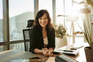 Femme souriante assise à un bureau